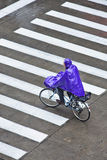 Cyclists dressed in rainwear in a wet Shanghai, China Stock Images