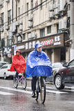Cyclists dressed in rainwear in a wet Shanghai, China. SHANGHAI–MAY 4, 2014. Cyclists dressed in rainwear in a rainy weather. Shanghai has a humid royalty free stock images