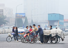 Cyclists and freight bikes with thick layer of smog in the air, Beijing, China Stock Photography