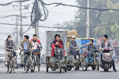 Cyclists and freight bikes with thick layer of smog in the air, Beijing, China Stock Photos