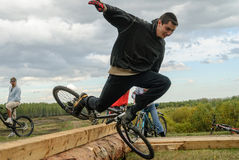 Cyclists jump through a log and falls Stock Photography