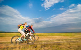 Cyclists in motion. Two cyclists biking in motion stock photo