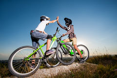 Cyclists with mountain bikes on the hill under blue sky Royalty Free Stock Photo