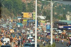 Bustling crowds amid shops in main intersection of downtown Kigali in Rwanda. Cyclists, pedestrians, shoppers, delivery trucks, satellite dishes, marketing signs stock image