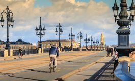 Cyclists and pedestrians stroll on the Bordeaux river bridge. Bordeaux, France - January 26, 2018 : cyclists and pedestrians stroll on the Bordeaux river bridge royalty free stock image