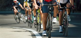 Cyclists with racing bikes during the cycling road race. When climbing uphill stock images