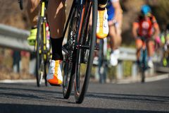 Cyclists with racing bikes during the cycling road race. Cycling competition,cyclist athletes riding a race,climbing up a hill on a bicycle Stock Images