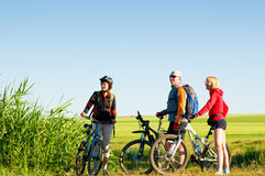 Cyclists relax biking outdoors. Mixed group of cyclists at sunrise royalty free stock images