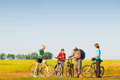 Cyclists relax biking outdoors. Mixed group of cyclists in field royalty free stock image