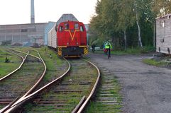Cyclists ride along the railway tracks, the red train is worth royalty free stock photos