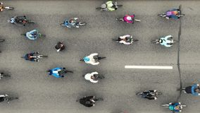 Cyclists ride along the road during the bike ride, aerial view vertically down. stock video