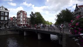 Cyclists ride on the bridge in old town stock video