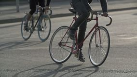 Cyclists ride fixie bicycles at city street. Ecological urban transport concept stock video footage