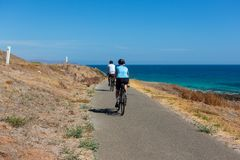 2 cyclists riding along the bike track at the beautiful Carrickalinga beach with rolling hills in the background on the Fleurieu P stock photo