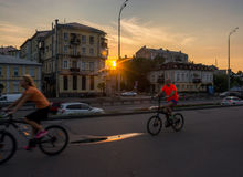 Cyclists riding along the waterfront, Ukraine, Kyiv. Editorial. 08.03.2017. Cyclists riding along the waterfront. Sunset between houses of old architecture on Royalty Free Stock Photo