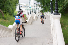Cyclists riding down a long flight of stairs Royalty Free Stock Photography