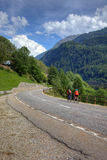 Cyclists on road in Alps, Europe. Cyclists on road among swiss alps, Europe Stock Image