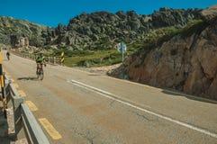 Cyclists on road passing through rocky landscape. Serra da Estrela, Portugal - July 14, 2018. Cyclists pedaling on roadway passing through rocky landscape, at stock photos