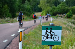 Cyclists on the road and traffic sign Stock Photography
