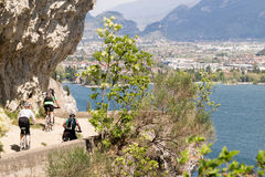 Cyclists run through the trail of Ponale in Riva del Garda, Ital Stock Photo