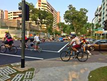 Cyclists in Singapore. Cyclists riding across a traffic light junction in Bukit Batok, Singapore stock photography