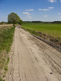 Cyclists in spring or summer dirt path Stock Image