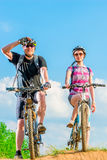 Cyclists stand on the mountain in the background of blue sky Stock Photo