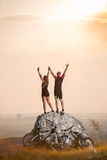 Cyclists standing on a large stone near mountain bikes Stock Image
