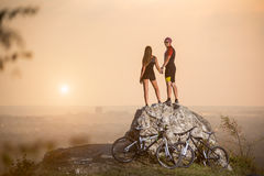 Cyclists standing on a large stone near mountain bikes stock photos