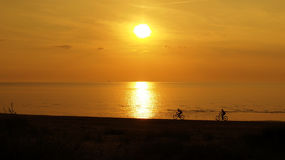 Cyclists on sea coast at orange sunset Stock Image