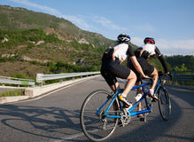 Cyclists on a Tandem bicycle riding uphill on a mountain roadway Royalty Free Stock Image