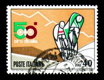 Cyclists uphill, 50th anniversary of Italy cycling race serie, c. MOSCOW, RUSSIA - APRIL 15, 2018: A stamp printed in Italy shows Cyclists uphill, 50th royalty free illustration