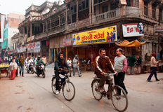 Cyclists on the vintage bircycles rush through the busy asian street Stock Images