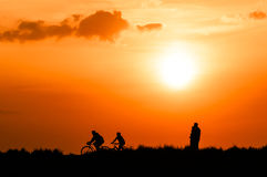 Cyclists and walkers at sunset. Silhouetted cyclists and walkers in countryside with orange sunset background stock image