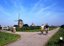 Cyclists and windmills, Kinderdijk. Stock Photography