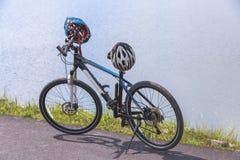 Cyclo arg cykel med en hjälm som står på vägen nära behållare royaltyfria bilder
