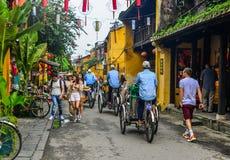 Cyclo dragende toeristen op hoofdstraat stock fotografie
