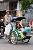 Cyclo driver and his passenger/customer. Phnom Penh, Cambodia, January 2, 2008, Cyclo driver peddling his passenger/customer and her shopping stock photo