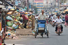 Cyclo driver peddling past garbage. Phnom Penh, Cambodia, January 2, 2008, Cyclo driver peddling past a man working in a garbage receptacle royalty free stock images