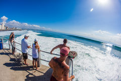 Cyclone Swells Surfing Jump Zone. Spectators and Surfer Rider on the end of beach pier watching a summer cyclone wave on a clear blue warm sunny day. The summer Royalty Free Stock Photo