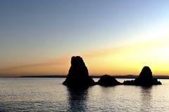 Cyclopean Isles i Acitrezza på solnedgången. royaltyfri fotografi