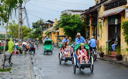 Cyclos carry tourists on street in Hoi An, Vietnam Stock Photo