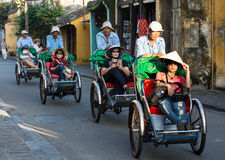 Cyclos carrying tourists on street in Hoi An, Vietnam.  Stock Photo