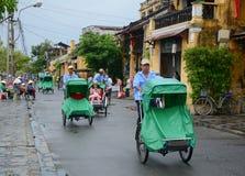 Cyclos de monte de personnes sur la rue principale en Hoi An, Vietnam Photographie stock