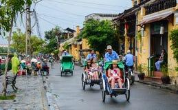 Cyclos portent des touristes sur la rue en Hoi An, Vietnam Photo stock