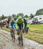 两Cyclsits在一条Cobbelstoned路在雨中 库存照片