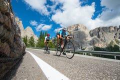 Cyclus bergaf - volgt de weg cirkelende man vrouw Stock Foto's