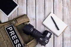 Cyfrowa kamera, notatnik z piórem, kamizelka kuloodporna i pastylka, dotykamy com Obraz Royalty Free