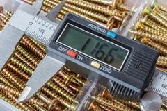 Cyfrowego elektroniczny caliper na tle rozpieczętowany składowy pudełko z kolor żółty śrub długim zbliżeniem fotografia stock