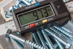 Cyfrowego elektroniczny caliper z sześciokąt głową czmycha na tle składowego pudełka zbliżenie zdjęcie stock